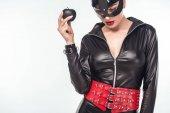 Verführerische junge Frau im Catsuit und Maske hält schwarz Apfel isoliert auf weiss