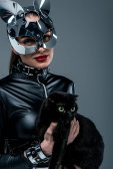 Geile Frau im sexy Kostüm und Maske hält schwarze Katze isoliert auf grau