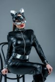 Attraktive heiße Mädchen in Catsuit und Maske posiert auf Stuhl isoliert auf grau
