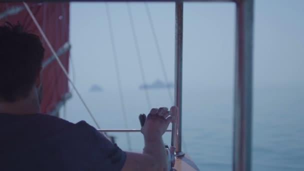 Kapitán na palubě velké lodi volant. Námořník u kormidla plachetnice. Jachty plachetní loď. Loď plující nad divokou vodu na otevřeném oceánu poblíž ostrovů Thajska.