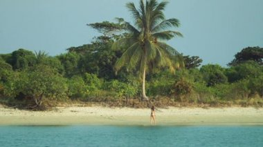 Girl walking barefoot on the water along deserted beach. Woman walking on a tropical beach. Young girl on an empty tropical beach on the deserted empty island. Ocean view, slow motion