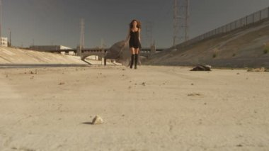 Beautiful girl with the waving fabric positing, dancing, running, walking in the LA River. Industrial area fashion videoshoot.