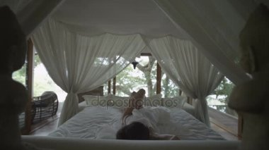 Sleeping girl wakes up. Romantic bed under the canopy. Bedroom in the forest. Woman stretches, yawning and waking up in bed. Wakes up and quickly gets out of bed. Overslept! Slow Motion