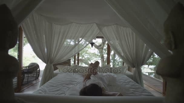 Schlafendes Mädchen wacht auf. Romantisches Bett unter dem Vordach. Schlafzimmer im Wald. Frau streckt sich, gähnt und wacht im Bett auf. Wacht auf und kommt schnell aus dem Bett. Verschlafen! zeitlupe