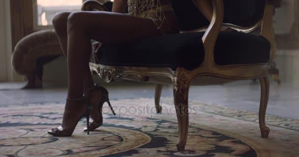 Dívka v flitr šaty a vysoké podpatky sedí na pohovce. Elegantní sexy holka na gauči