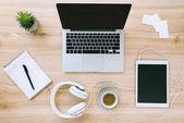 Laptop, Tablet und Kaffeetasse am Arbeitsplatz