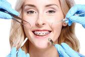 Kezei fogorvos eszközök közelében nő