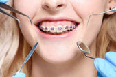 Zahnarzt Instrumente vor Mund mit Hosenträgern