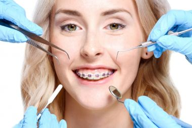 Hands holding dentist tools near woman