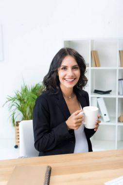 Pregnant businesswoman with cup of hot drink
