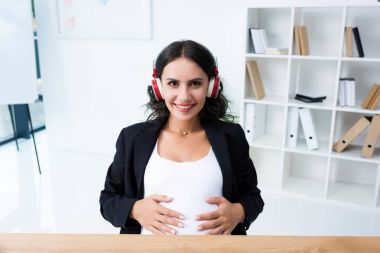 Pregnant businesswoman listening music in headphones