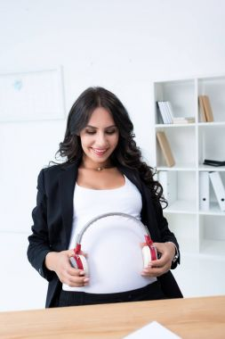 Pregnant businesswoman with headphones on tummy