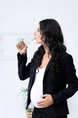 pregnant businesswoman drinking water