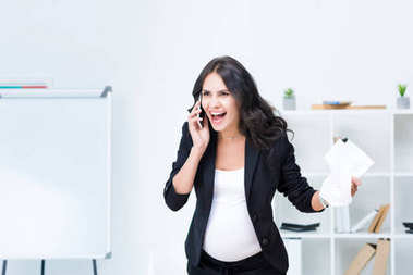 Pregnant businesswoman shouting at phone