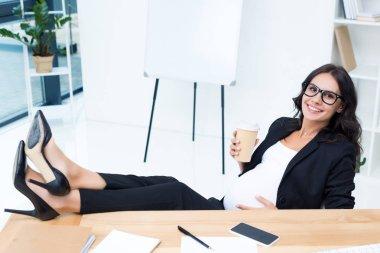 pregnant businesswoman drinking coffee