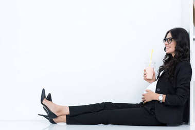 Pregnant businesswoman drinking milkshake