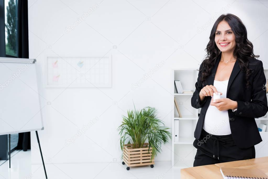 pregnant businesswoman with jar of pills