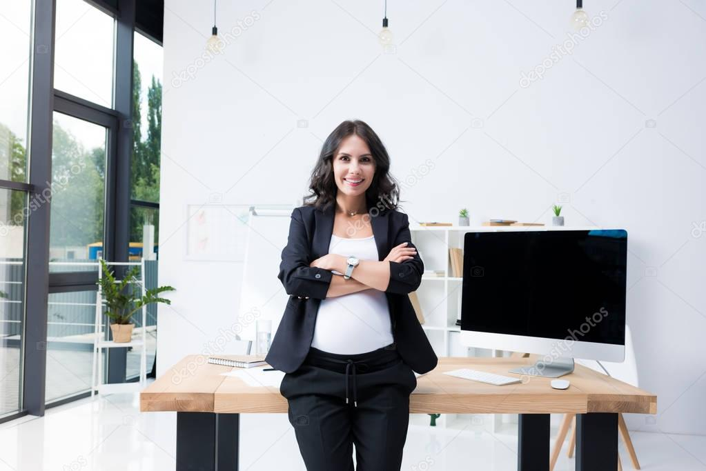 Pregnant businesswoman with crossed arms