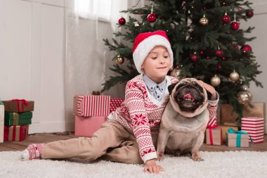 boy petting his dog on christmas