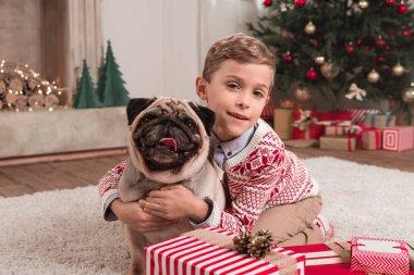 boy embracing pug on christmas
