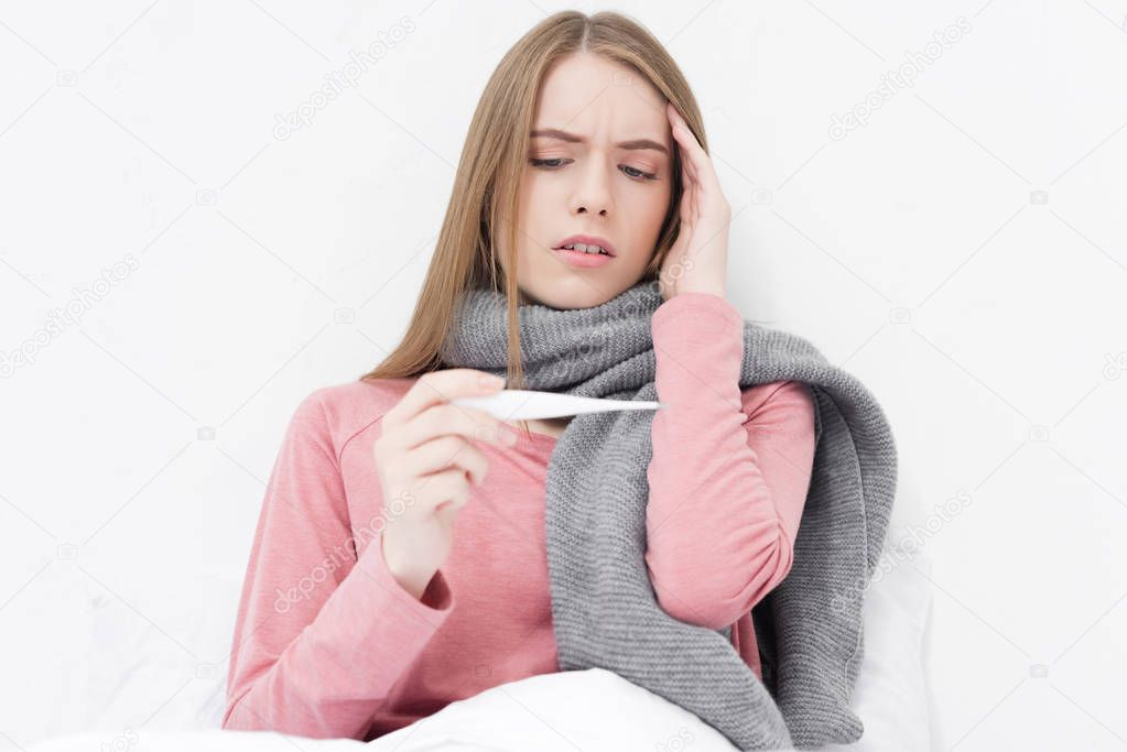 Sick girl looking on thermometer