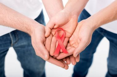 gay couple holding aids ribbon