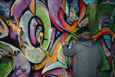 Hátulnézet utcai művész festészet graffiti aeroszolos festékkel falon éjjel