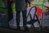 nízké část pouliční umělec Malování graffiti na zdi v noci