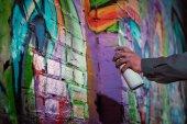 oříznutý pohled pouliční umělec Malování graffiti s aerosolové barvy na zeď v noci