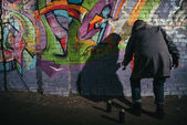 rear view of street artist painting graffiti with aerosol paint on wall at night
