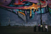 Photo colorful graffiti on wall cans with aerosol paint standing on foreground
