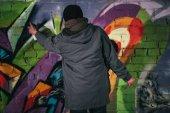 zadní pohled na člověka Malování graffiti s aerosolové barvy na zeď v noci