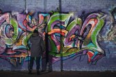 Hátulnézet utcai művész festmény színes graffitik a falon éjjel