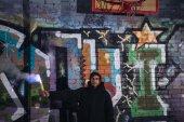 muž drží kouřové bomby a stojí proti zdi s graffiti v noci