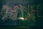 Fotografie osoby držící kouřové bomby a stojí proti zdi s graffiti v noci