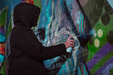 anonymous painting graffiti with aerosol paint on wall at night