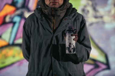 cropped view of man holding can with aerosol paint at night