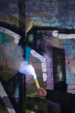 cropped view of hand with smoke bomb against wall with graffiti at night
