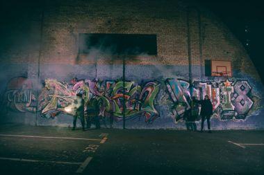 """Картина, постер, плакат, фотообои """"люди, держащие дымовые шашки и стоящие у стены с граффити ночью """", артикул 176153928"""
