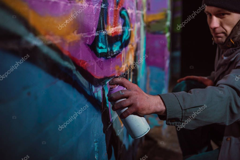 man painting graffiti with aerosol paint on wall at night