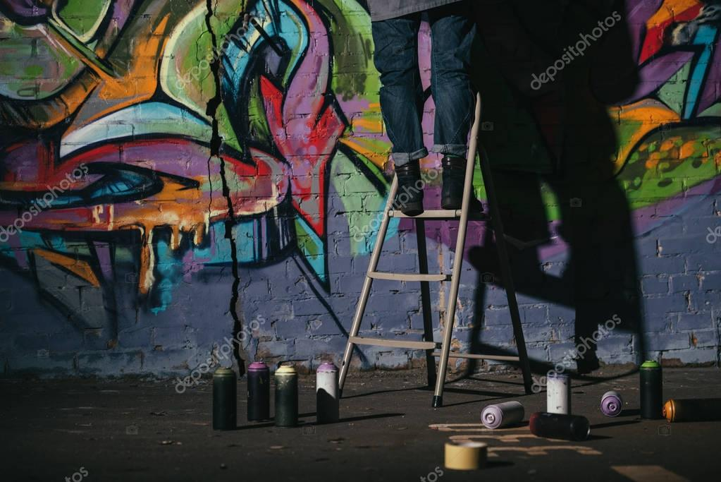 cropped view of standing on ladder and painting colorful graffiti at night