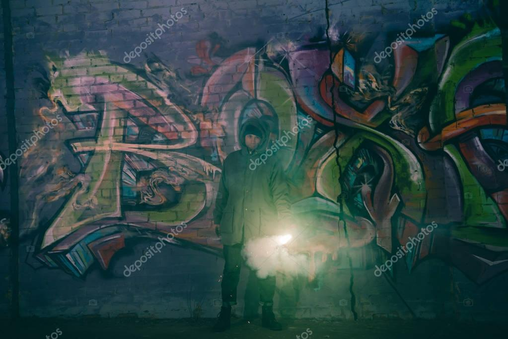 man holding smoke bomb and standing against wall with graffiti at night