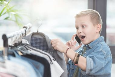 Surprised boy using smartphone while holding cloth in hand at shop stock vector