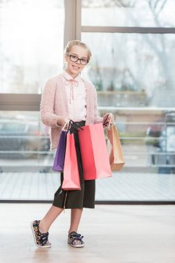 smiling child in glasses holding colored paper bags at shop