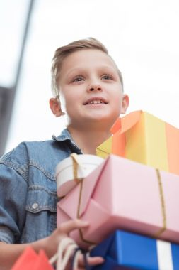 smiling boy holding stacked boxes with paper bags in hands at shop