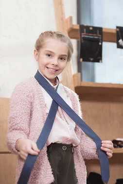 smiling child holding textile stripe wrapped over her neck at shop
