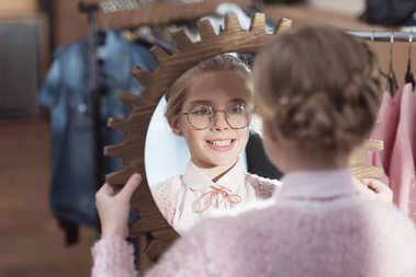 happy child looking at mirror in her hands at store interior