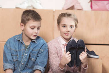 sister holding pair of shoes in hands while sitting near brother at store