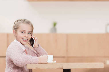 smiling kid sitting with cup in hands and using smartphone while looking at camera