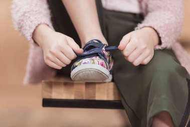 cropped image of child tying lace on sneaker while sitting